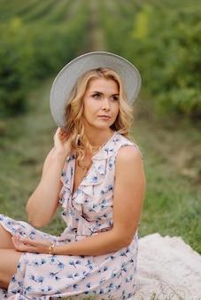 Giovane donna alla moda in vestito e cappello dall'annata blu rosa che posa nel campo verde