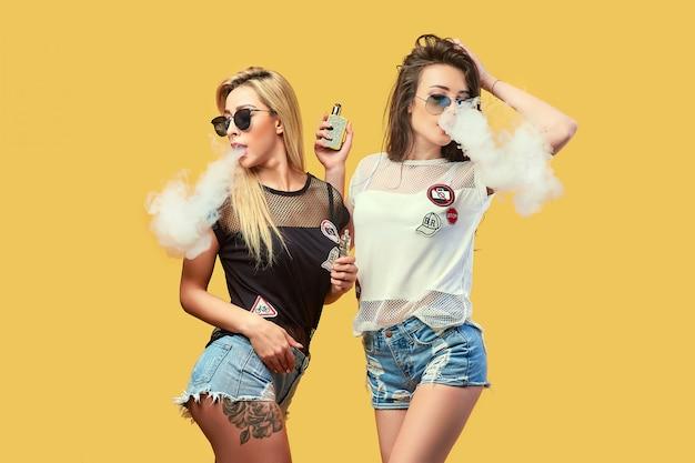 Giovane donna alla moda nel fumo degli occhiali da sole