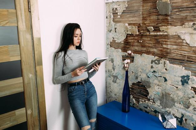 Giovane donna alla moda si appoggia alla rivista di lettura della parete
