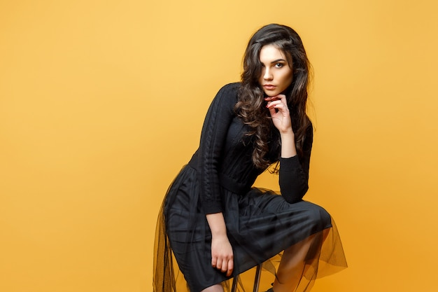 Giovane donna alla moda sulla sedia