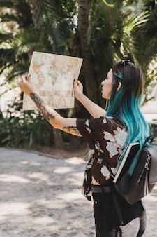 Giovane donna alla ricerca di direzione nella mappa