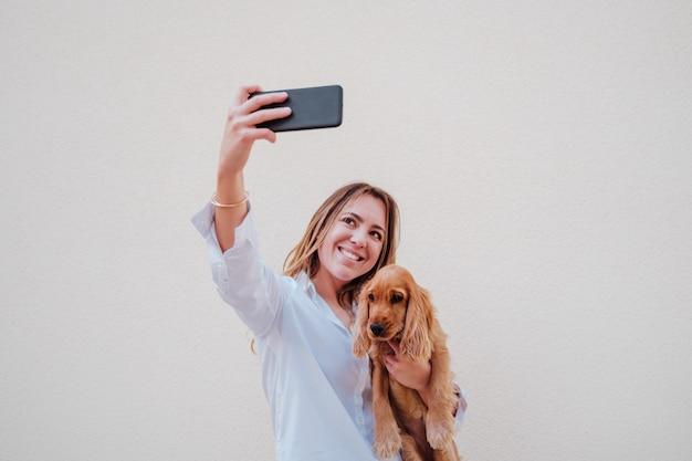 Giovane donna alla strada con il suo cane cocker scattare una foto con il cellulare. stile di vita all'aperto con animali domestici