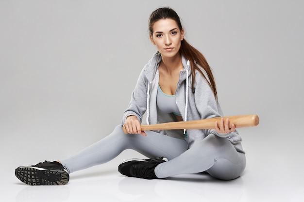 Giovane donna allegra brutale in abiti sportivi che si siedono con il pezzo sul bianco.