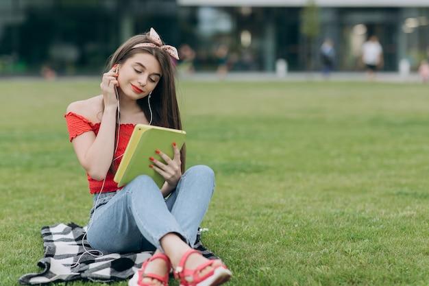 Giovane donna allegra che ascolta la musica. la giovane donna ascolta la canzone sul lettore musicale