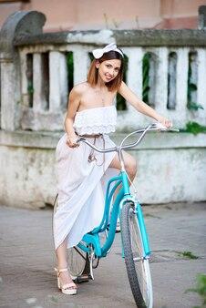 Giovane donna allegra che cicla nella città che sorride allegro