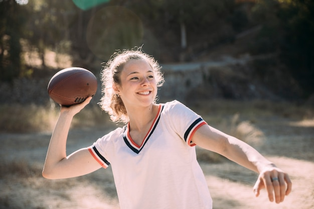 Giovane donna allegra che gioca rugby