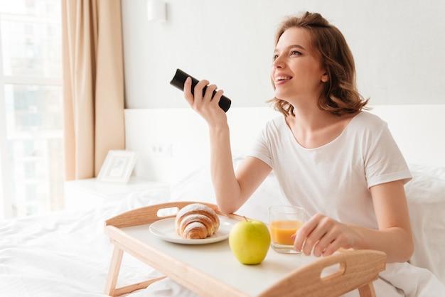 Giovane donna allegra che guarda il telecomando della tenuta della tv.