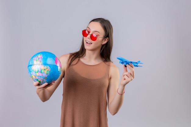 Giovane donna allegra che indossa occhiali da sole rossi che tengono globo e aeroplano giocattolo giocoso e felice in piedi su bianco