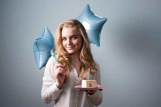 Giovane donna allegra che mangia torta di compleanno