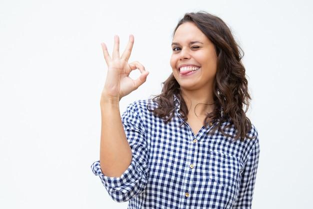 Giovane donna allegra che mostra segno giusto