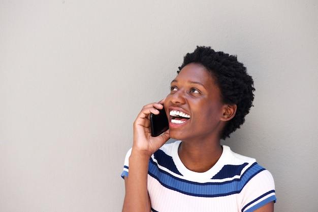 Giovane donna allegra che parla sul telefono cellulare contro fondo grigio