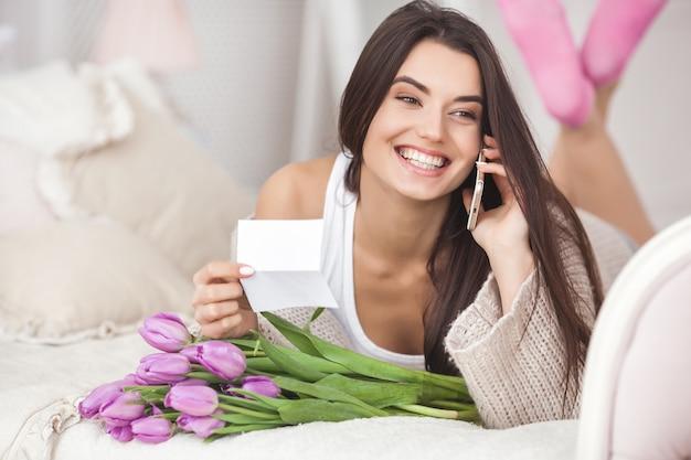 Giovane donna allegra che parla sul telefono e che tiene i fiori. bella signora con tulipani