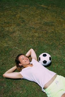 Giovane donna allegra che riposa al campo di calcio