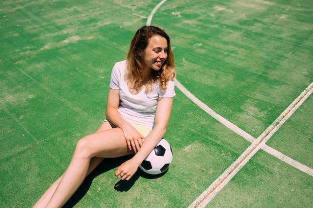 Giovane donna allegra che si siede con la sfera di calcio