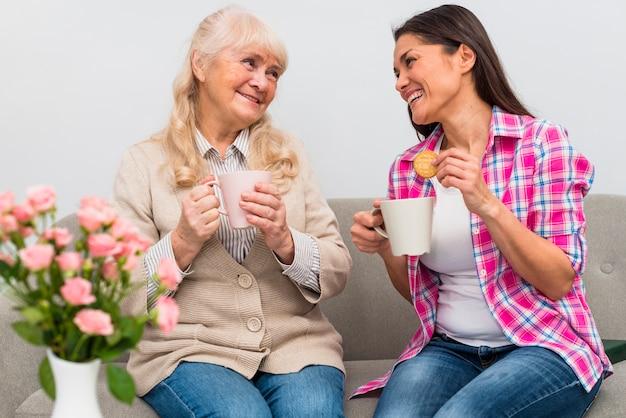 Giovane donna allegra che si siede con sua tazza di caffè della holding della madre