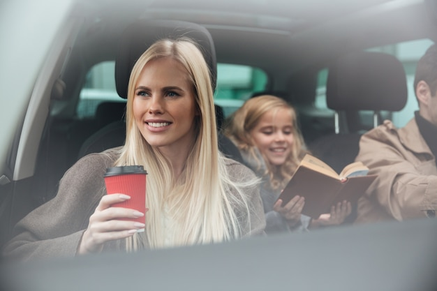 Giovane donna allegra che si siede in automobile