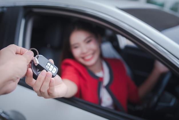 Giovane donna allegra che si siede in un'automobile con le chiavi a disposizione - concetto affitta un'automobile