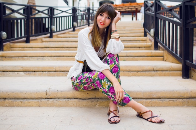 Giovane donna allegra che si siede sui gradini, vestito luminoso estivo alla moda, acconciatura alla moda. atmosfera di vacanza. stampa tropicale. ritratto alto vicino fresco.