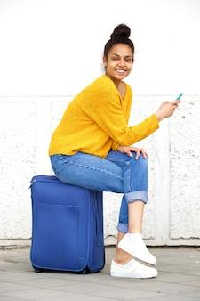 Giovane donna allegra che si siede sulla borsa di viaggio con il telefono cellulare