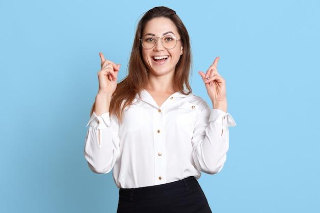 Giovane donna allegra che trova nuova idea e che alza il dito indice