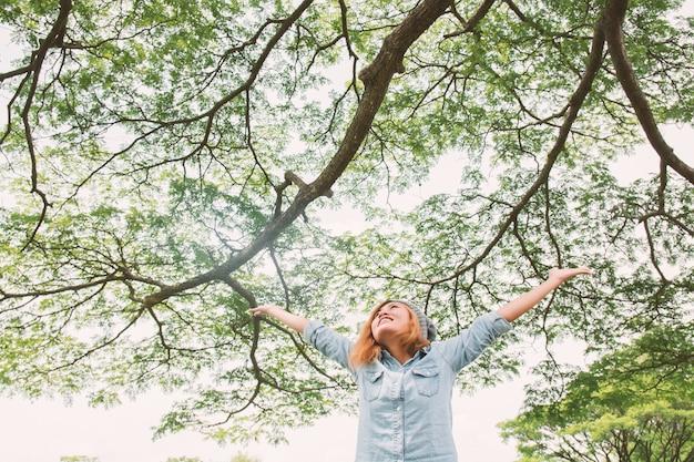 Giovane donna allegra con i rami albero di fondo