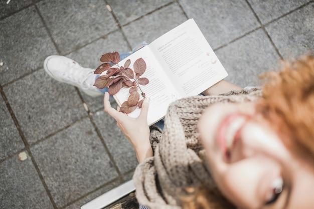 Giovane donna allegra con il libro e le foglie di autunno