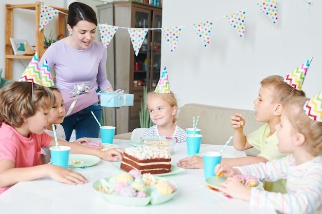 Giovane donna allegra con regali di compleanno in piedi a tavola con un gruppo di bambini piccoli e saluti a casa festa