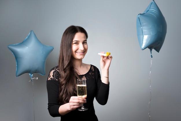 Giovane donna allegra con vetro e corno del partito