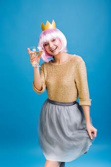 Giovane donna allegra divertente con capelli rosa tagliati, champagne che esprime positività. corona d'oro sulla testa, gonna in tulle grigio, applausi, grande festa di compleanno, emozioni positive del viso.