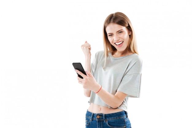 Giovane donna allegra felice che tiene telefono cellulare e che celebra una vittoria