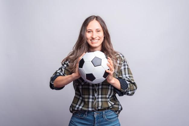 Giovane donna allegra in camicia che tiene pallone da calcio sul muro bianco.