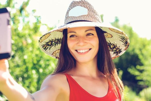 Giovane donna allegra in cappello che prende selfie con il telefono cellulare sulla stazione turistica estiva