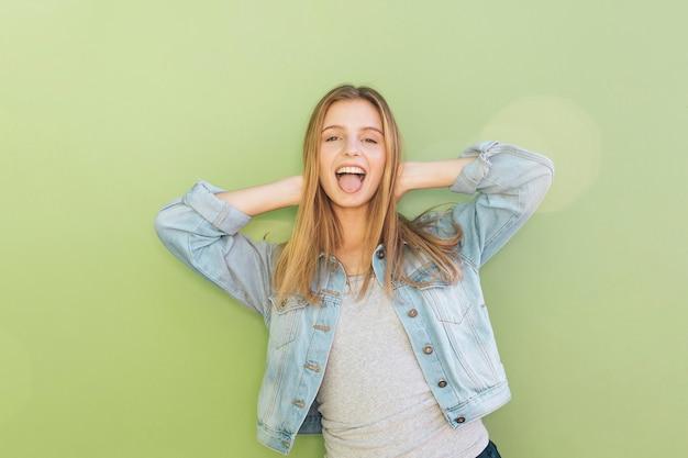 Giovane donna allegra in giacca blu con le sue mani dietro la testa contro il contesto verde