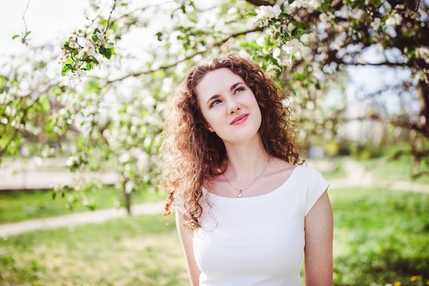 Giovane donna allegra in una maglietta bianca sotto l'albero di fioritura.
