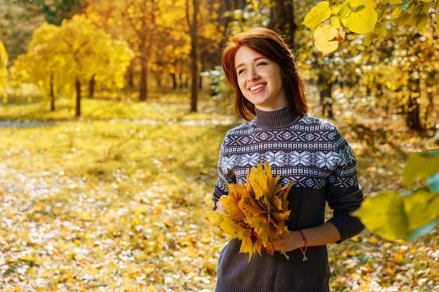 Giovane donna allegra nella sosta di autunno che sorride un giorno soleggiato.