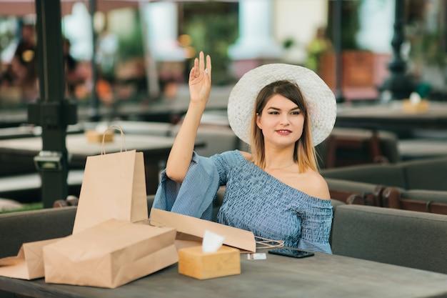 Giovane donna allegra shopaholic in calore e vestito seduto in un bar all'aperto e chiede al cameriere di venire in ordine