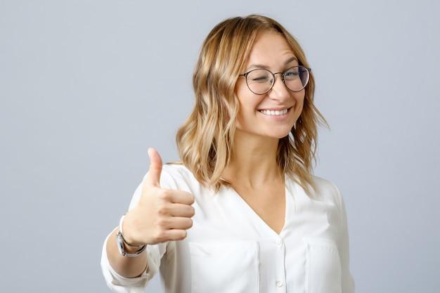 Giovane donna allegra sorridente felice che mostra i pollici in su