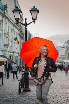 Giovane donna allegra sotto un ombrello rosso nel centro urbano in autunno
