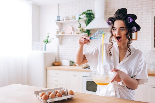 Giovane donna allegra stupita osserva le uova gialle che lei mescola. stai in cucina e meraviglia. uova in contenitore sulla tavola. da solo nella stanza bianca. daylight.