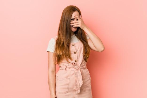 Giovane donna allo zenzero con le lentiggini che sbatte le palpebre attraverso le dita