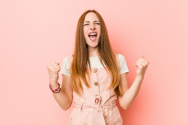 Giovane donna allo zenzero con lentiggini tifo spensierato ed eccitato. concetto di vittoria.