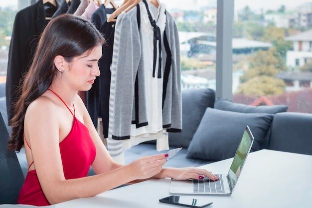 Giovane donna amichevole caucasica che lavora con il computer portatile e che vende acquisto in linea di commercio elettronico