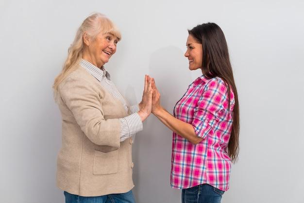 Giovane donna amichevole che dà livello cinque alla sua madre senior che sta contro il fondo bianco