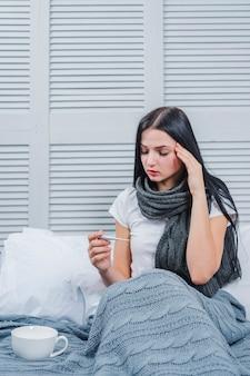 Giovane donna ammalata che si siede sul letto che esamina termometro