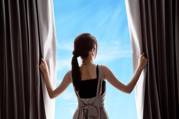 Giovane donna apertura tende e cielo blu