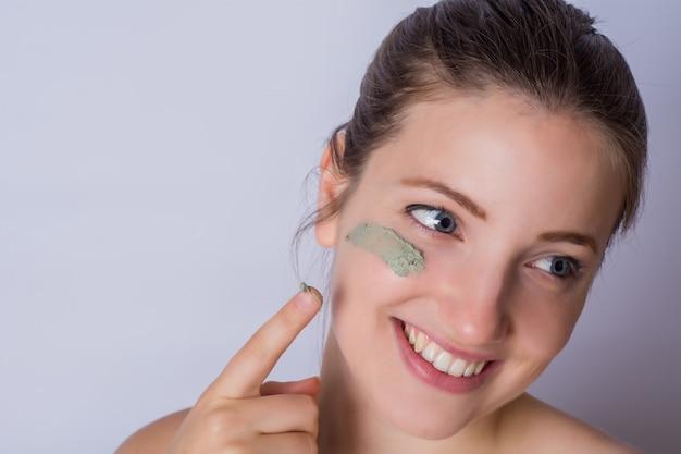 Giovane donna applicando polvere di fondazione.