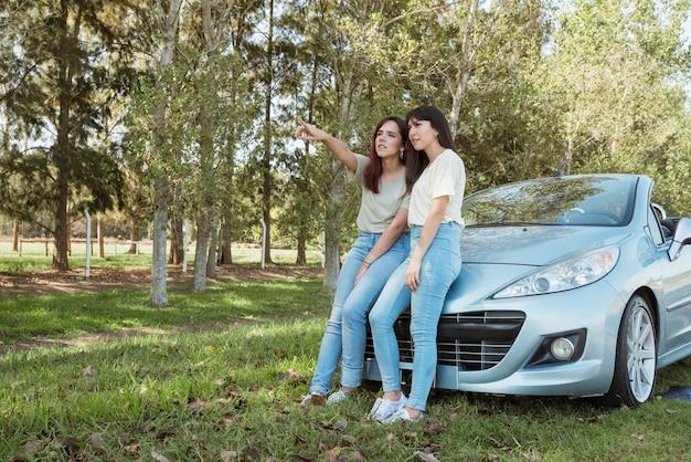 Giovane donna appoggiata alla loro auto