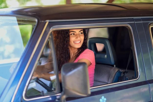 Giovane donna araba alla guida di un vecchio furgone in natura
