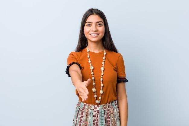 Giovane donna araba che allunga mano alla macchina fotografica nel gesto di saluto.