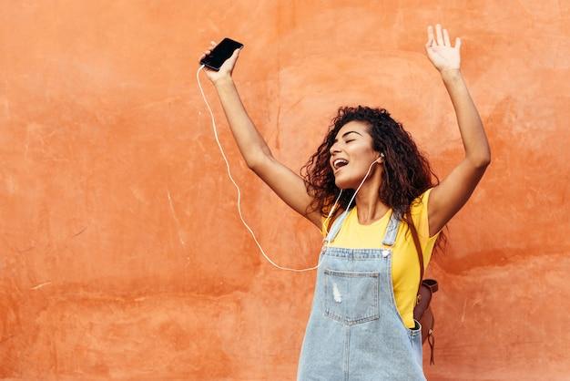 Giovane donna araba che ascolta la musica con i trasduttori auricolari all'aperto